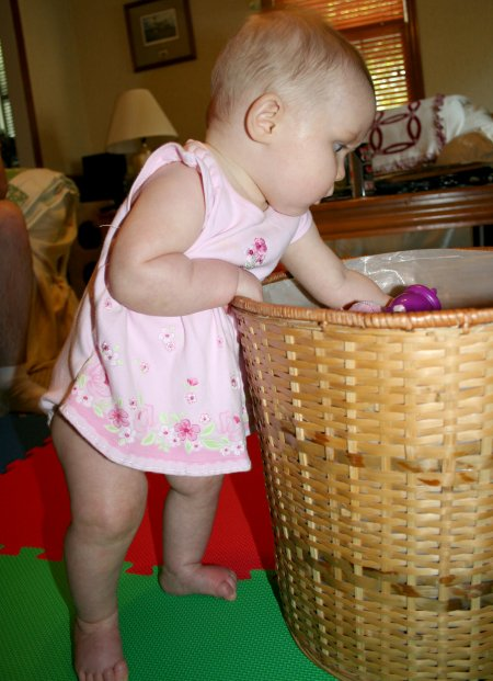 [Cate standing with the help of her toy basket]